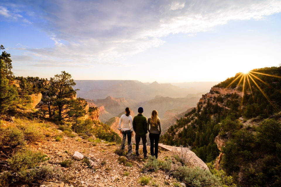 Three hikers look over the rim at sunset at the Grand Canyon